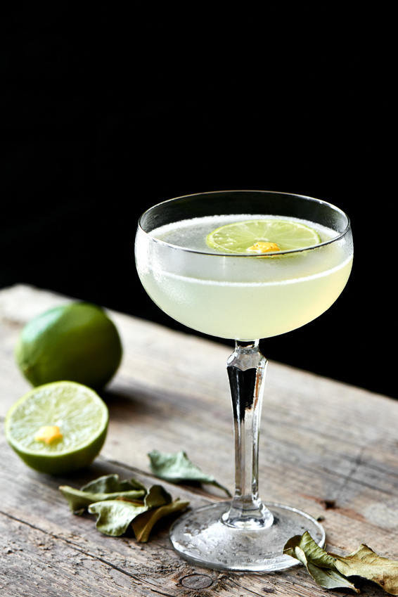 The glass of alcoholic cocktails Daiquiri consists of rum on the leaves of lime, elderflower syrup stands on wooden table on black background