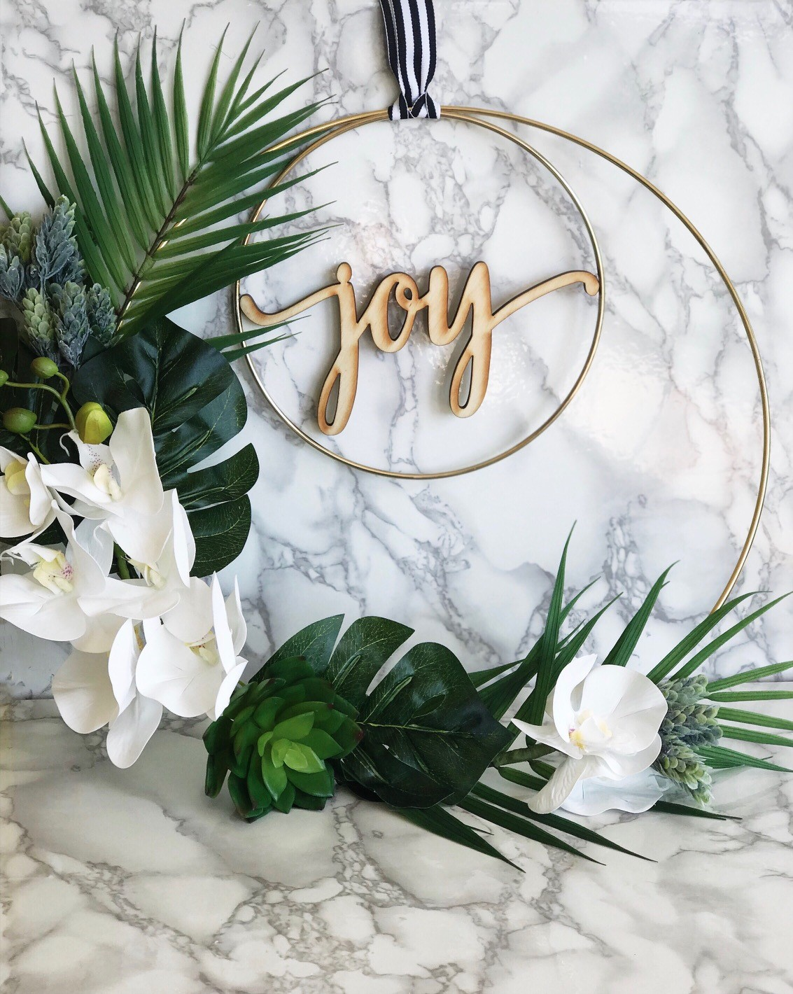 DIY Tropical Wreath for Christmas - gorgeous faux leaves, succulents and orchids make up this simple modern wreath